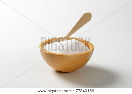 pure sea salt in the wooden bowl with immersed teaspoon