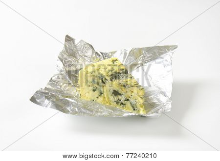 unwrapped triangle of blue cheese in the aluminum foil