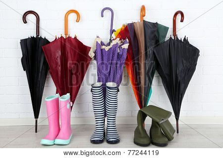 Bright umbrellas leaning against a bricks wall and gumboots