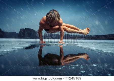 Man doing yoga exercise (parsva bakasana) on the ice of frozen lake at winter snowy day