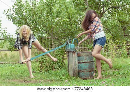 Blonde and brunette soaking each other with water