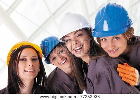 Young female construction workers with protective clothes and helmets. Isolated with work path.