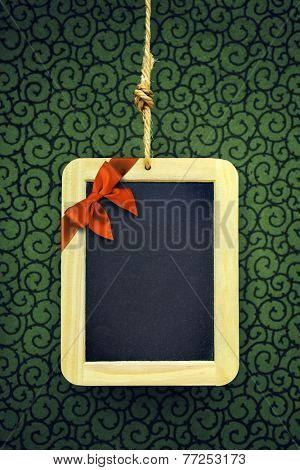 Hanged old slate board with Christmas bow in the corner