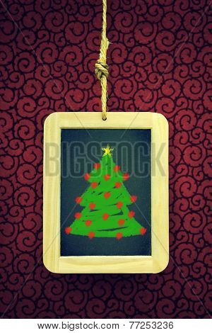 Hanged old slate board with Christmas tree chalk drawing