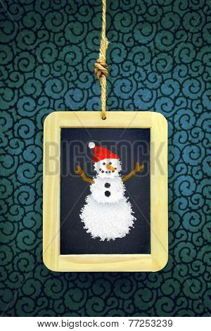 Hanged old slate board with Christmas snowman chalk drawing