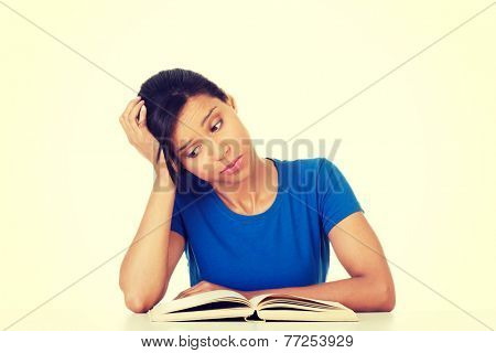Woman studying at the desk being tired, isolated on white