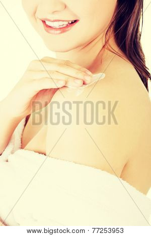 Attractive woman rubbing body lotion on arm. Wrapped in towel. Isolated on white.