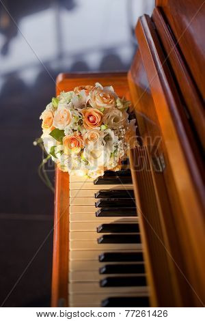 Pastel wedding bouquet with orange roses on piano