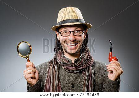Funny detective with smoking pipe and magnifying glass