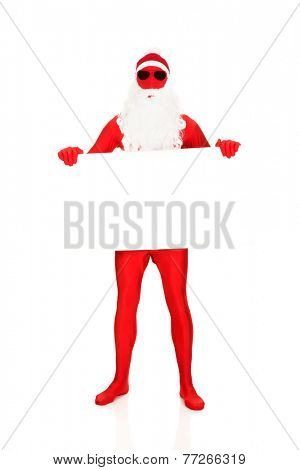 Full length santa in latex clothes holding empty banner.