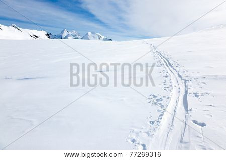 Ski tracks on the fresh snow of a large glacier. In background with the peaks of Monte Rosa massif - Zermatt, Switzerland, Europe.