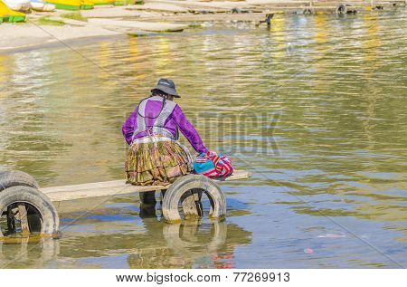 COPACABANA, BOLIVIA, MAY 7, 2014: Local woman in traditional attire sits on jetty in port (Titicaca lake)