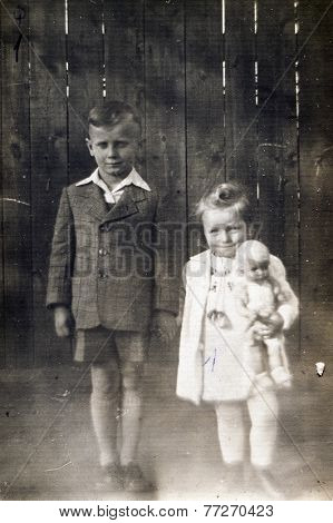 GERMANY, CIRCA 1930s - Vintage photo of brother and sister with a doll