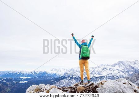 Female hiker with backpack raised her hands celebrating successful climb to top of mountain