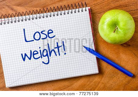 Lose weight written on a notepad with a pen