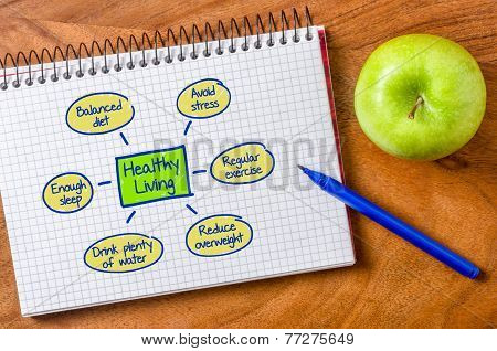 Healthy living written on a notepad with a pen