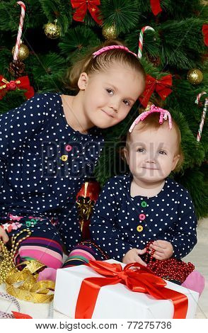 Two little girls at a Christmas fur-tree with gifts