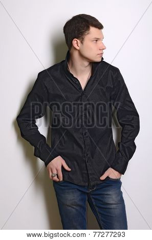 Fashion portrait of young cute man in black shirt poses over wall