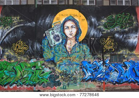 graffiti of attractive girl with boom box on her shoulder