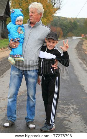 grandfather and two his grandchildren in rural landscape, autumn