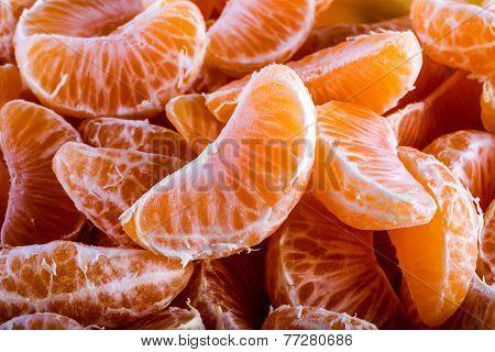 Tangerine or mandarin orange segments peeled close up background texture.