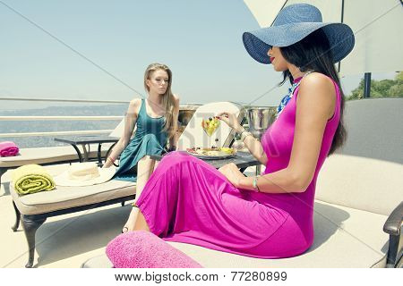 two stylish girls sitting in beach chairs enjoying the tropical weather / summer holidays and vacati