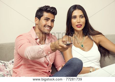 Young middle eastern couple watching tv on a sofa
