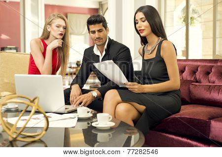 Portrait of a handsome fashionable man with two charming women in a business meeting