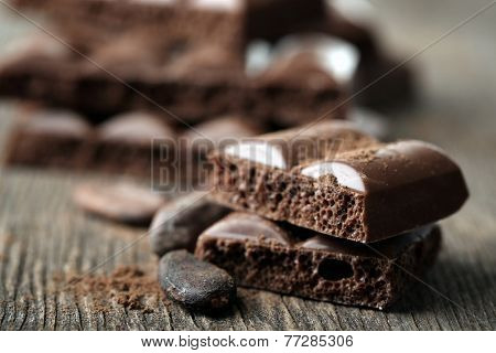 Tasty porous chocolate with cocoa beans, on wooden table