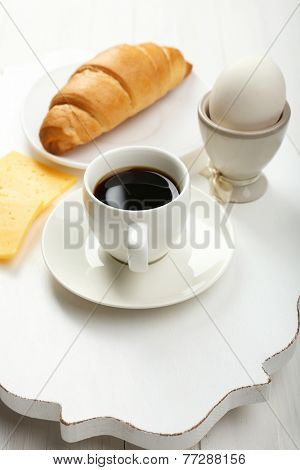 Delicious breakfast with coffee, fresh croissant, egg and cheese