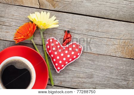 Cup of coffee, heart toy and gerbera flowers on wooden table with copy space