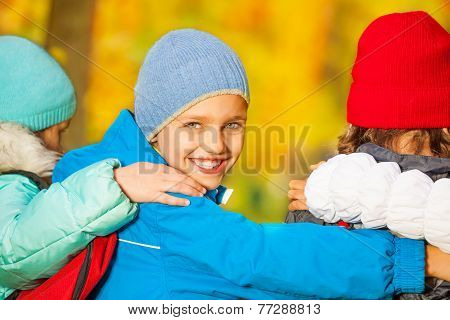 Boy look back with his friends hugging close
