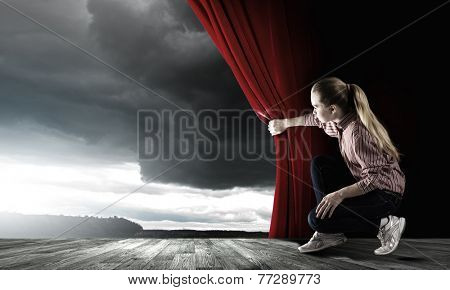Young woman in casual opening drape curtain
