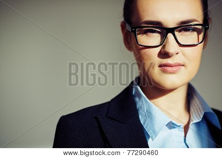 Young businesswoman in eyeglasses looking at camera