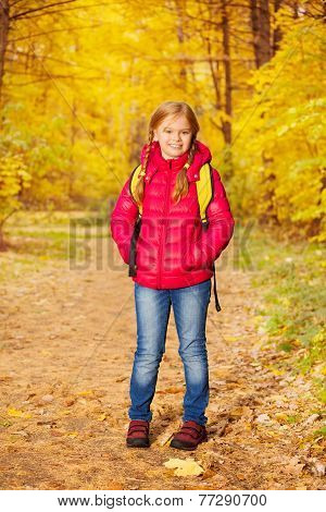 Small girl wears rucksack and stands in forest