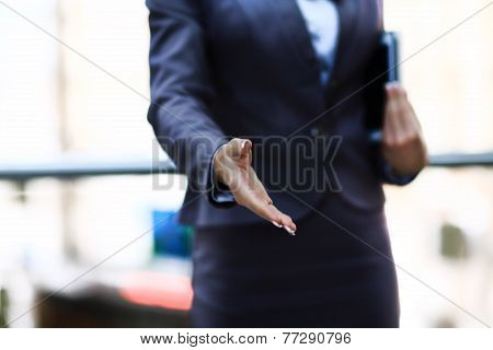 Business womans hand reaching out for handshake