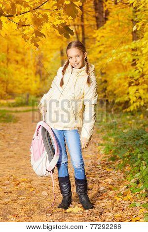 Beautiful girl holding rucksack standing in forest