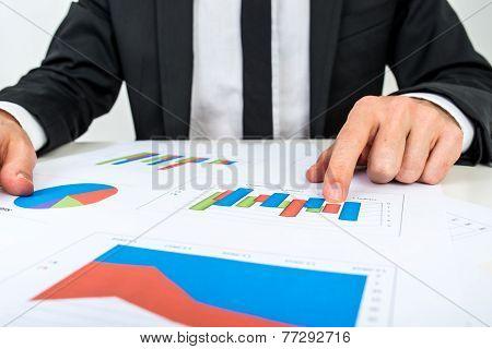 Businessman Analysing A Set Of Bar Graphs