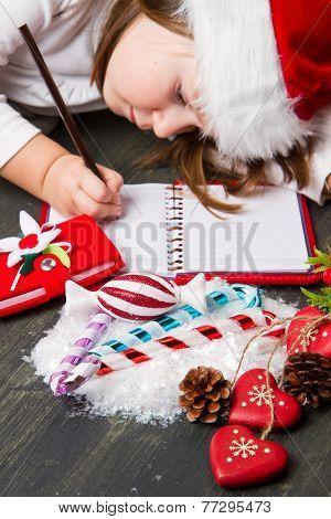 Funny girl in Santa hat writes letter to Santa near christmas decoration
