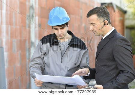 Contractor on building site checking different points with worker