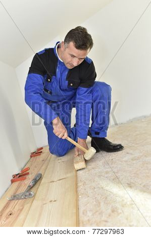 Craftsman putting wooden floor in room