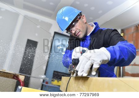 Closeup of carpenter cutting wood with electric saw