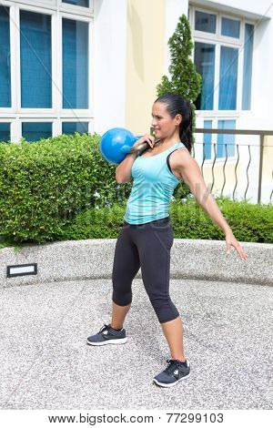 Beautiful sporty hispanic woman in blue training with kettlebell doing the clean routine