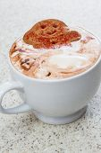 picture of ginger bread  - close up of a ginger bread man relaxing in a cup with hot chocolate and whipped cream - JPG