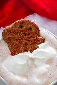 stock photo of ginger bread  - close up of a ginger bread man relaxing in a cup of hot chocolate with whipped cream - JPG