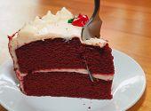 stock photo of red velvet cake  - Fork plunging into a red velvet cake on a white plate - JPG
