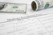 pic of medicare  - A Medicare healthcare enrollment form and money - JPG