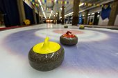 stock photo of indoor games  - Curling stone on ice of a indoors rink - JPG