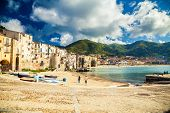 stock photo of old boat  - empty old beach of Cefalu with fishing boats Sicily Italy - JPG