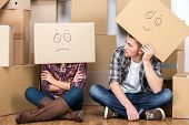 pic of smiley face  - Couple with cardboard boxes on their heads with smiley face are sitting on floor after the moving house - JPG